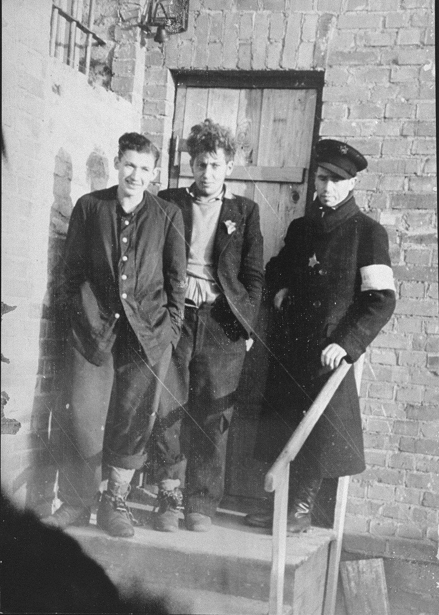 Two prisoners and a Jewish policeman standing in front of the ghetto jail. The two men were arrested on orders from the Gestapo for theft outside of the ghetto. For lack of proof, they were released by the Jewish police and sent to the underground to hiding.