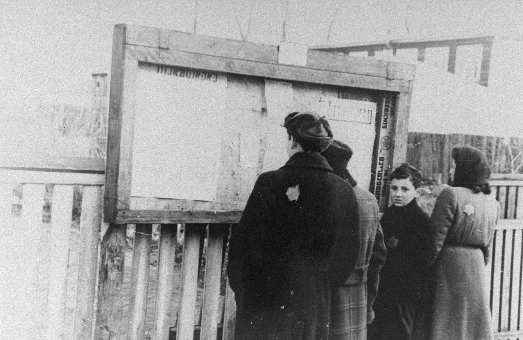 A small group of Jews reads the announcements posted by the Jewish Council in a display box on a street in the Kovno ghetto.   The boy on the right is probably Yankele Bergman, one of the child messengers of the Jewish Council.
