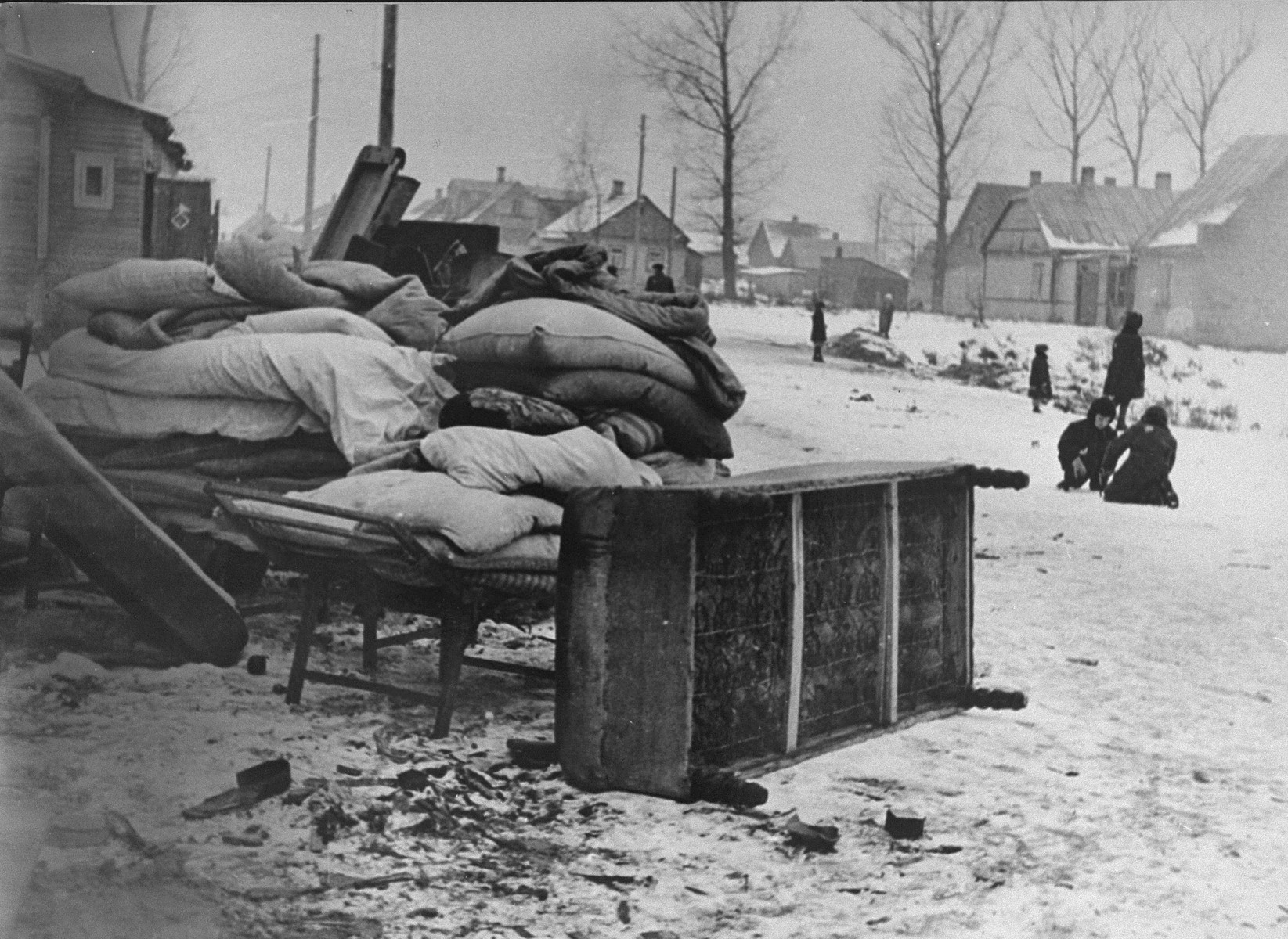 Bedding and furniture piled up on a residential street in the Kovno ghetto.