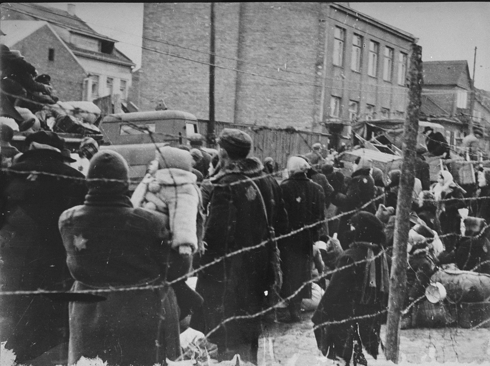 Jews in the Kovno ghetto who have been assembled for deportation, look on while their luggage is loaded onto trucks.
