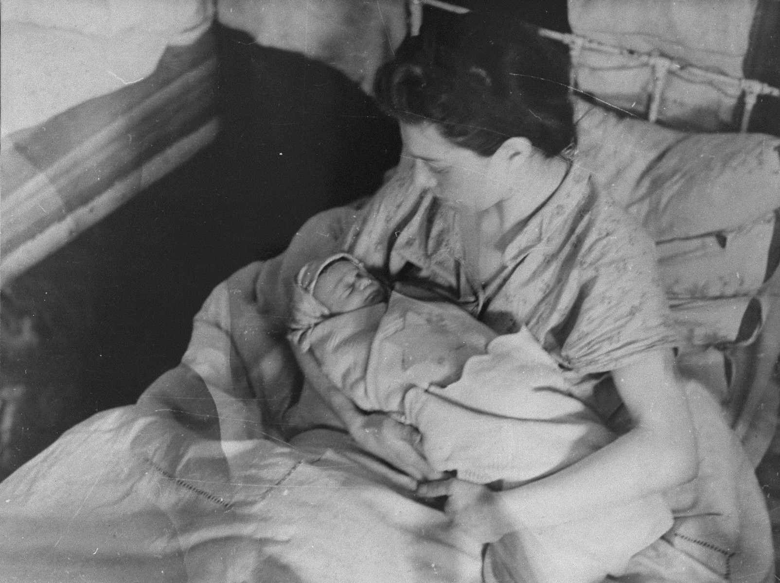 A mother cradles her new born baby in the Kovno ghetto hospital.  The child is swaddled in a blanket with a Star of David.