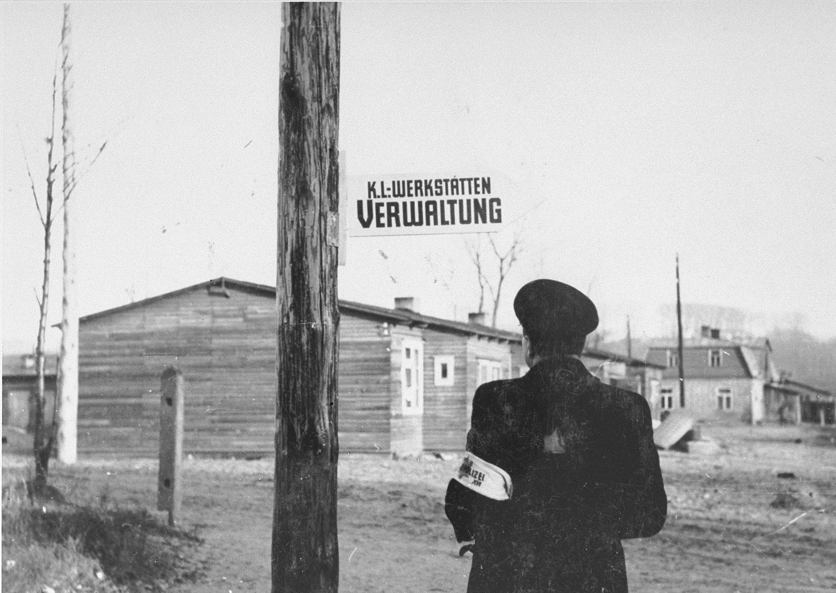 "Jewish policeman next to the workshops in the Kovno ghetto once the ghetto had officially become a concentration camp.   The K-L on the sign stands for ""Konzentrations lager""."
