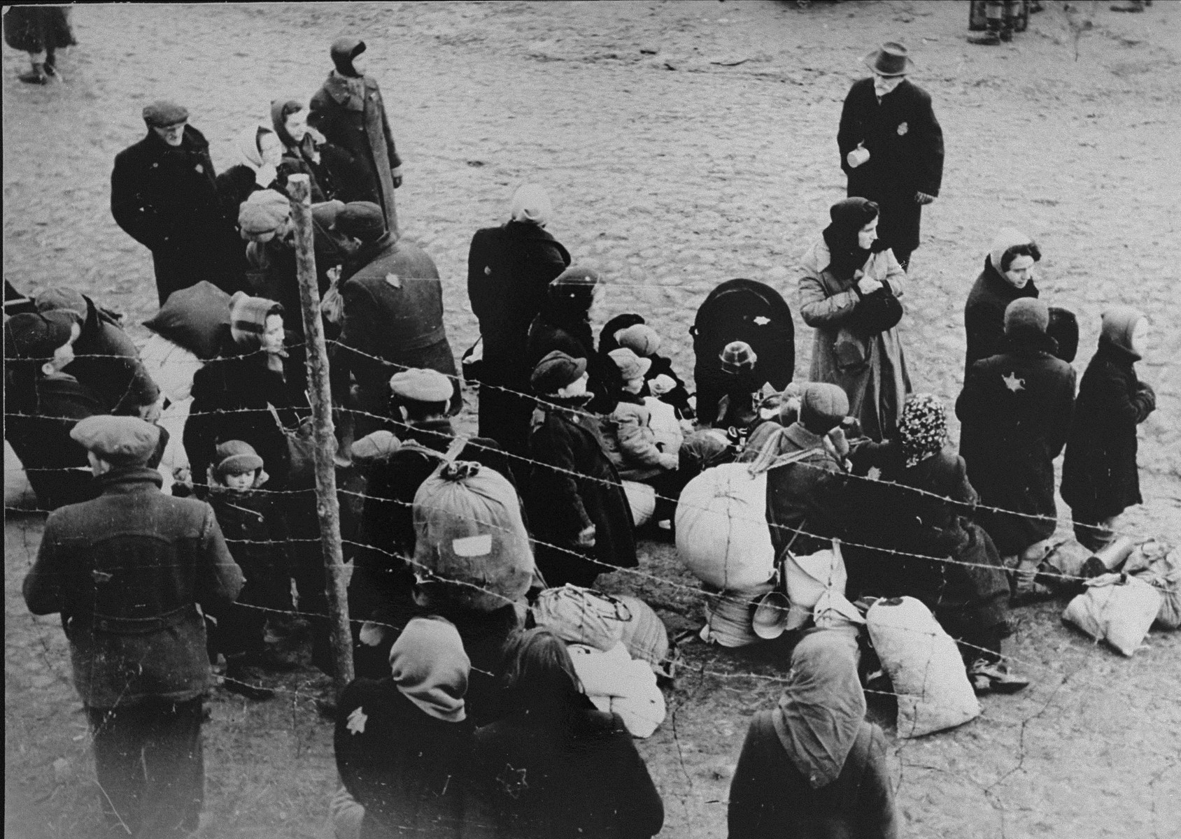 A group of Jews is gathered at an assembly point in the Kovno ghetto during a deportation action.   [Though the photo seems to be part of the series of the deportation to Estonia, the family has been identified as the Ipp family who were sent to Riga.  Among those pictured may be Jacob Ipp (now Ipson, the boy standing on the left, behind the barbed wire fence), his mother, Etta (Butrimowitz) Ipp (standing behind him), and Chananya Butrimowitz (Etta's father, carrying a backpack).]