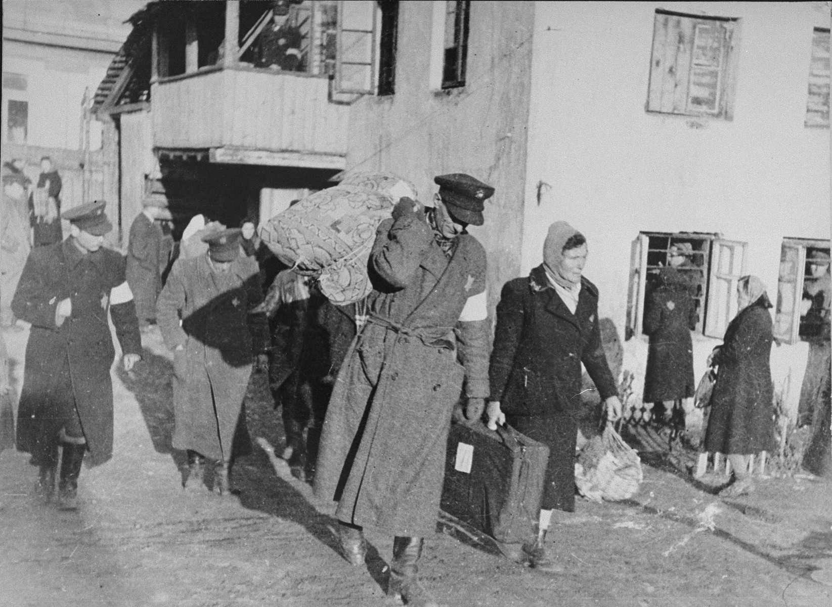 A Jewish policeman helps a family carry their luggage from the Abba Haskel synagogue to the assembly point for deportation in the Kovno ghetto.