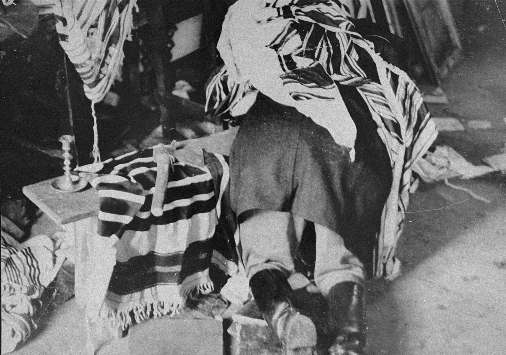 Synagogue vandalized by Lithuanians during June, 1941 pogrom in Kovno. A man, covered with a prayer shawl, lies over a bench in the synagogue. A hatchet is on the bench next to him.