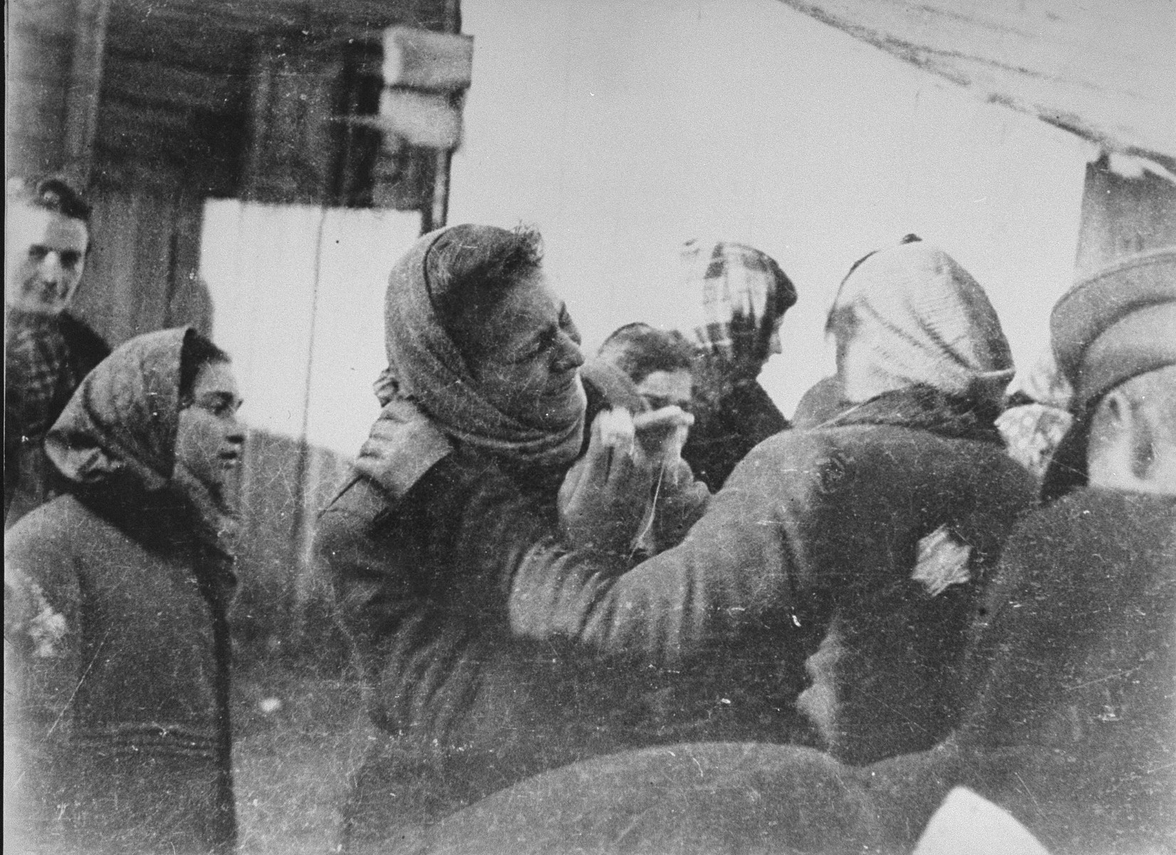Two women bid each other farewell at an assembly point in the Kovno ghetto during a deportation action to Estonia.