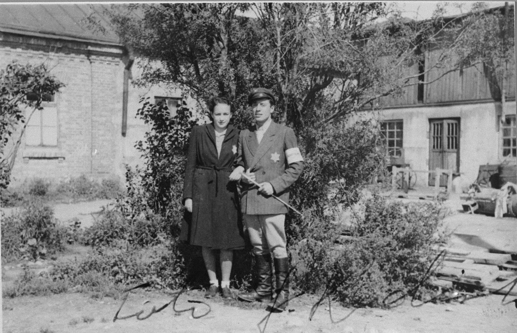 A Jewish policeman poses with his wife outside a home in the Kovno ghetto.  Pictured are Itzhak Dembin and his wife Rita Benyaminowicz-Dembin.  He was killed in the Ninth Fort, and she died in a burning bunker during the liquidation of the Kovno ghetto.