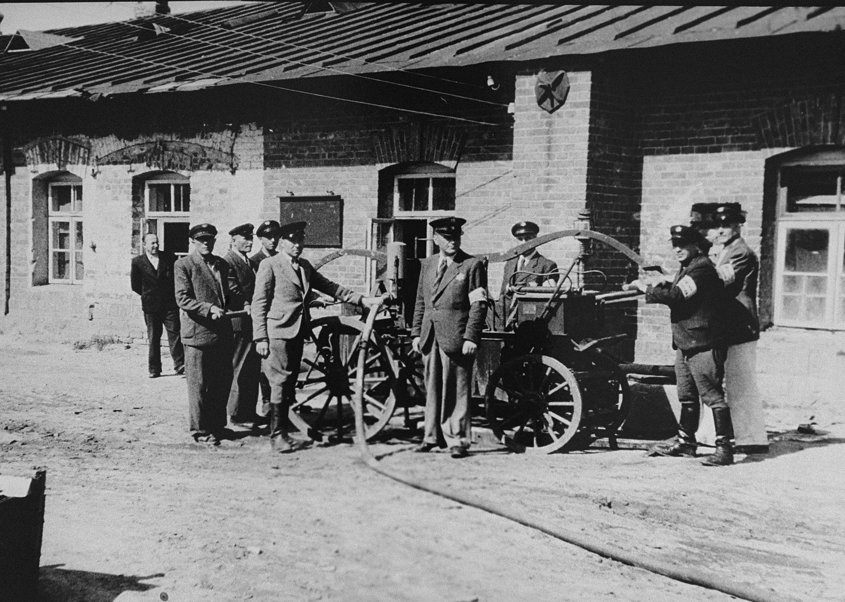 Members of the Jewish fire brigade in the Kovno ghetto pose outside around their fire vehicle.    Among those pictured is Yankel Kaplan (at the far right).