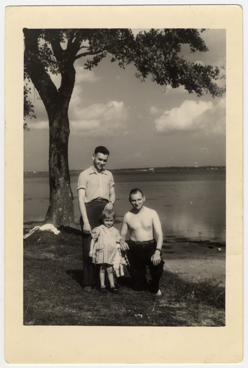 Group portrait of two Latvian Jewish men with a young child standing by the Daugava River after liberation.  On the left is Leo May and on the right is Lazar Javorkovsky.  The two men survived concentration camp together.