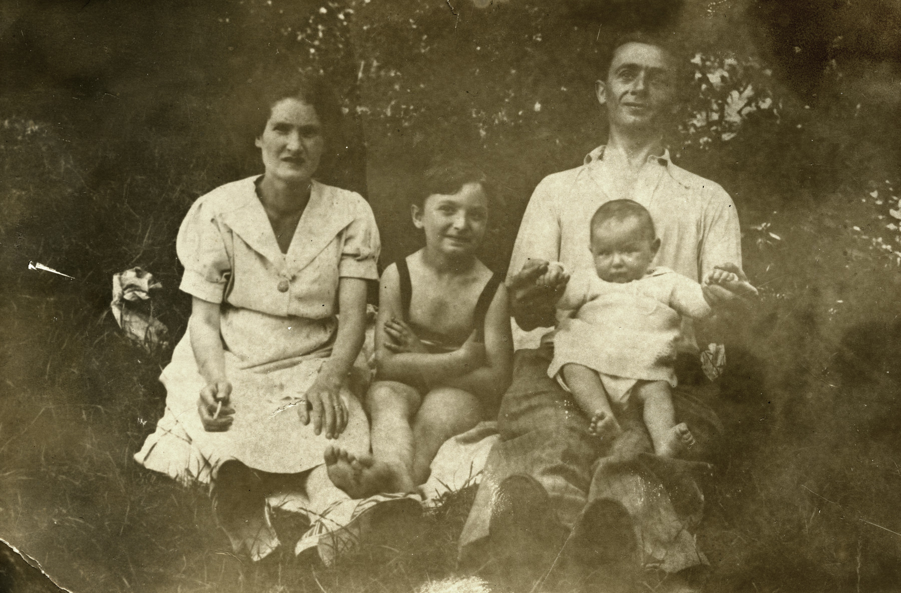 Portrait of the Rosensweig family sitting outdoors.  This is the last photo of the family taken with the father.  From left to right are Elizabet, Lisa, Max Mendel and Ida.