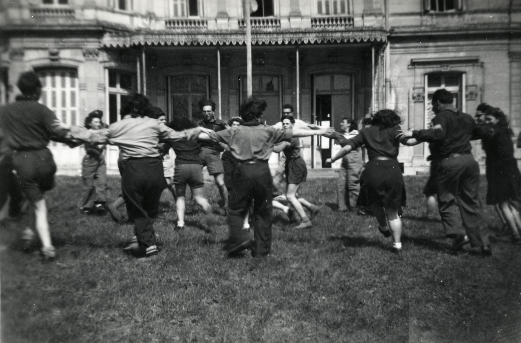 Zionist youth belonging to the Kvutza Borochov dance a horah on the lawn of their hachshara outside of Paris.
