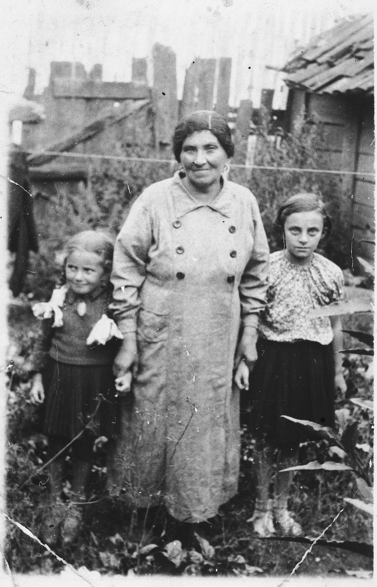 Sara Tyk (the mother of Shmuel) stands with two young girls in her yard.