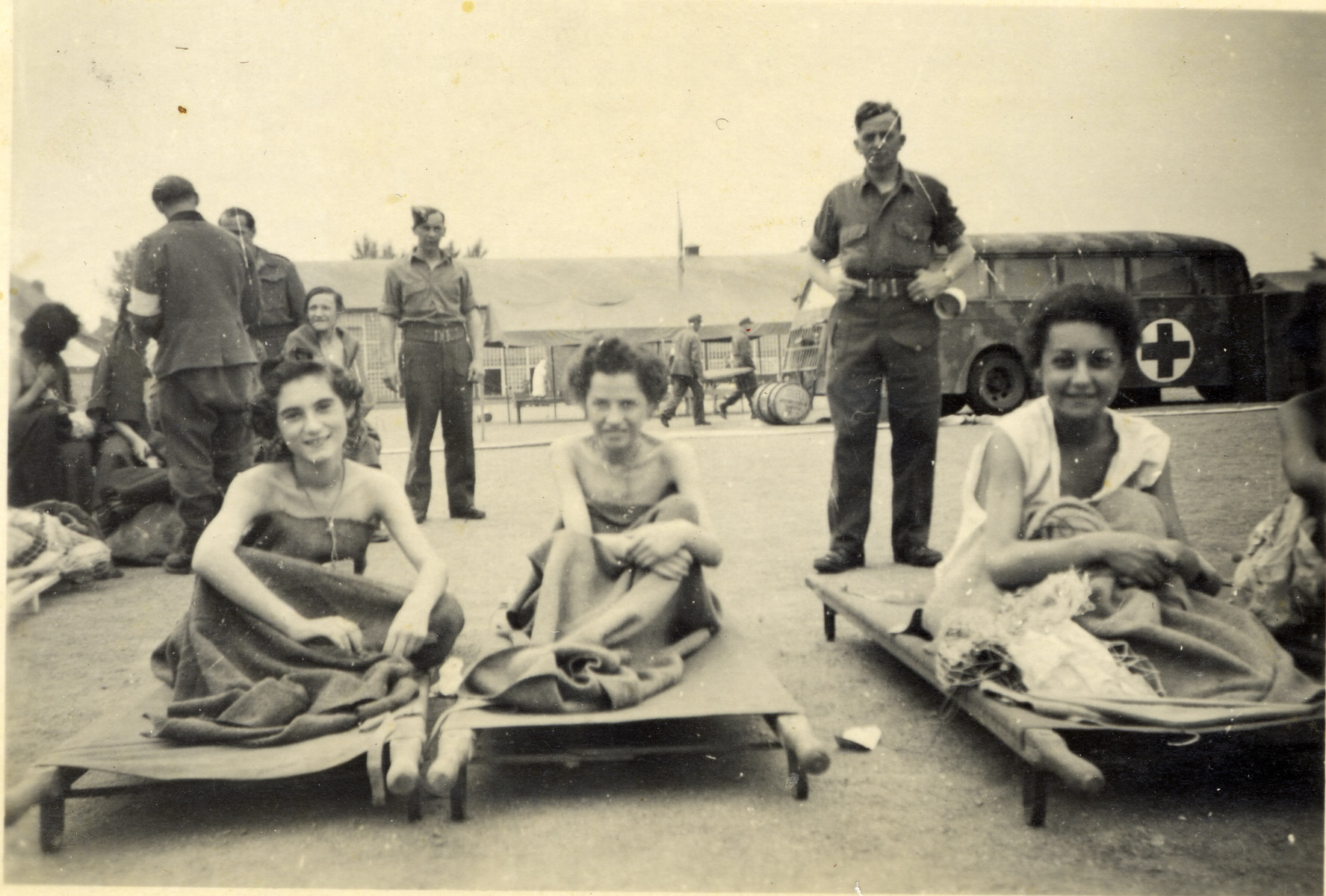 Three women sit outside on stretchers in front of an aid workers group and an ambulance