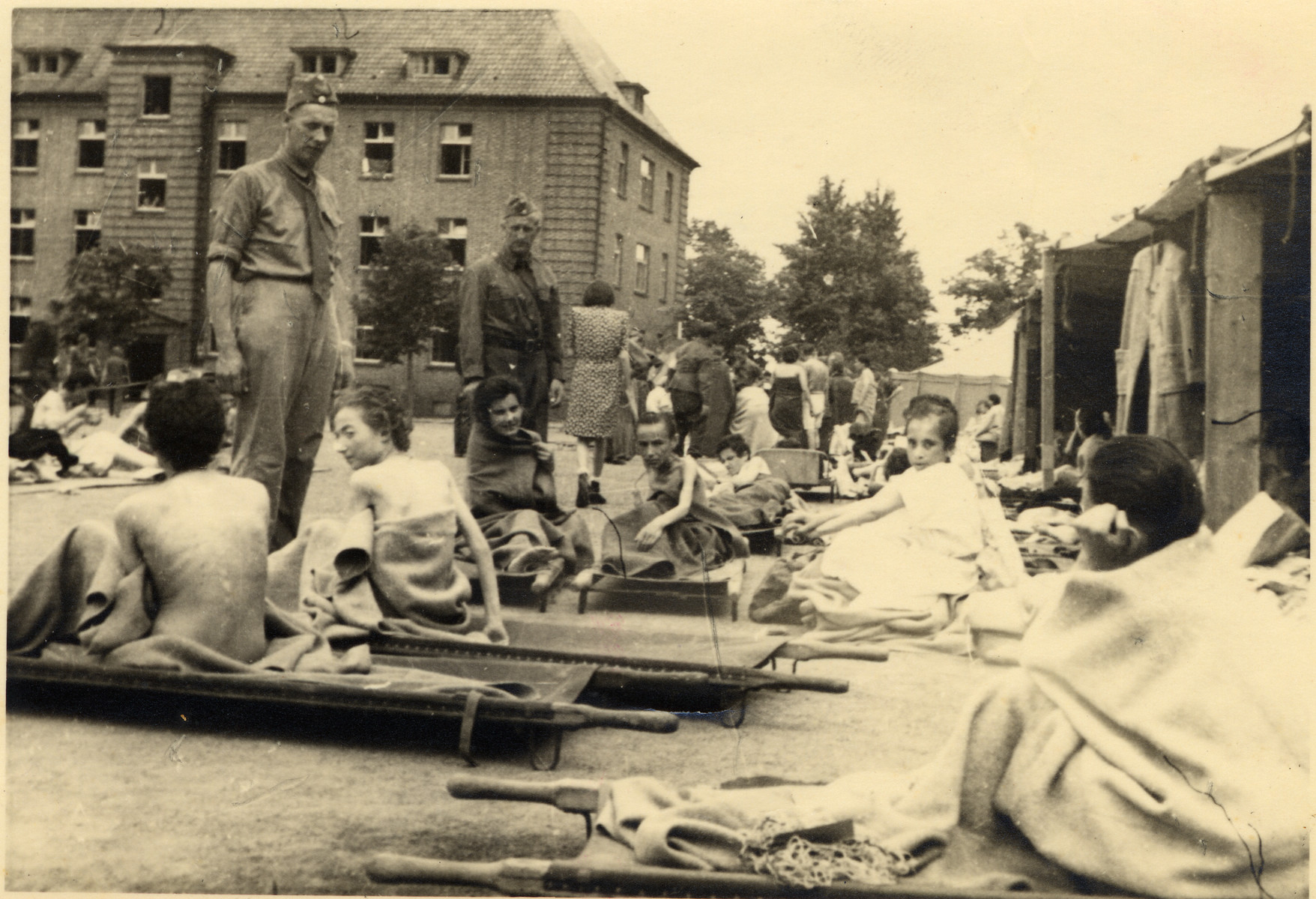 Survivors of Bergen-Belsen sit on stretchers while waiting on medical treatment.
