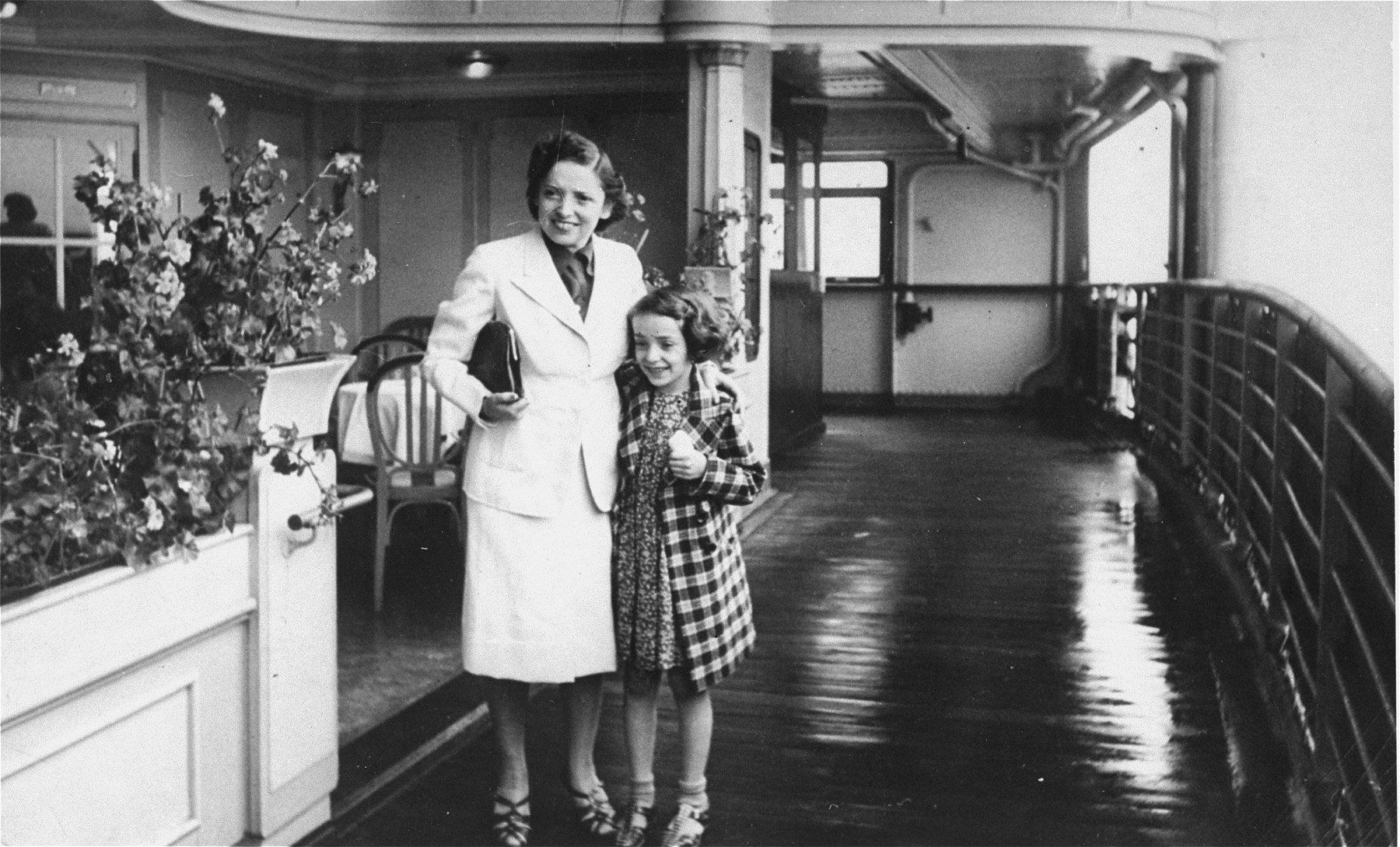 Elly Reutlinger and her nine-year-old daughter Renate, passengers on the MS St. Louis, pose near a dining area on the ship.