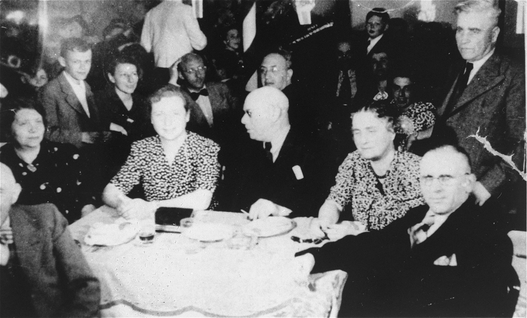 St. Louis passengers sit at a table in the ship's dining room.   Josef Josph is pictured on the right; his wife Lily is next to him.  Karl Simon is third from the right at the table and his wife Selma Simon is fourth from the right.