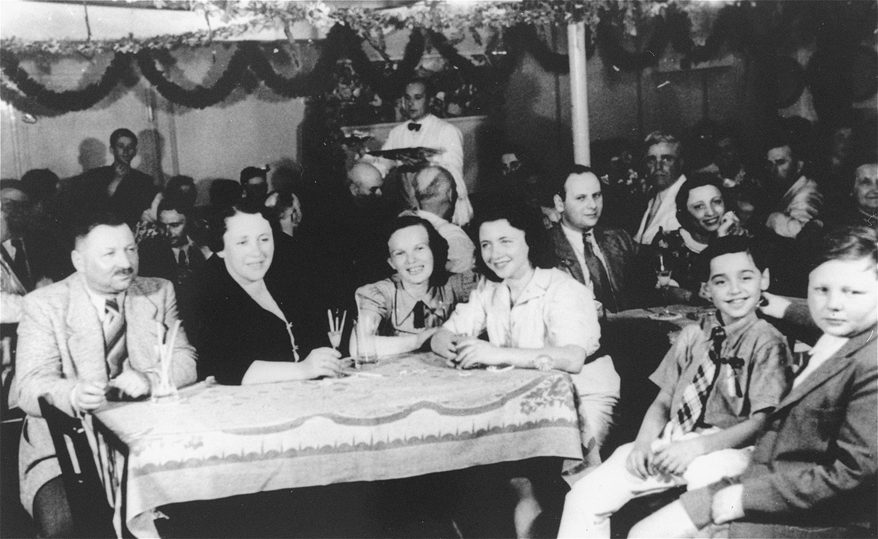 Passengers in the dining room of the MS St. Louis.    Pictured in the foreground from left to right are: Joseph Guttman, Mrs.Guttman, Ilse Karliner, Rose Guttman, Henry Goldstein (Gallant), Harry Guttman.  Behind, at the right, are Alfred and Sophie Aron.