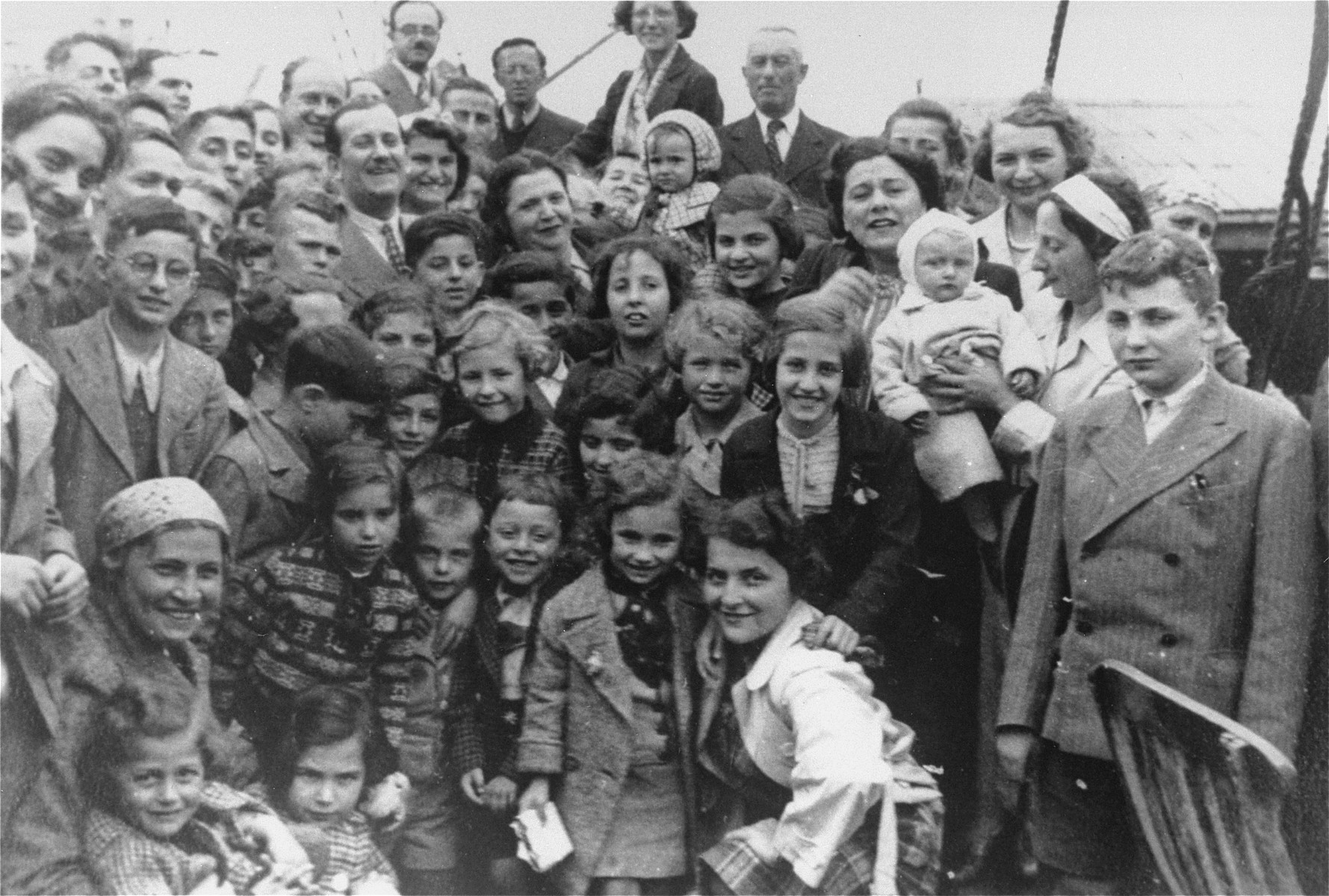 Passengers aboard the MS St. Louis.  Liane Reif, is standing at center, foreground.  Her brother Fred is standing first from the right.  Among the other passengers are Liesl Loeb, Herbert Karliner, Troper, Hans Fischer, Lisl Mandel, Henry Gallan, Judl Gunther and Oskar Blechner.