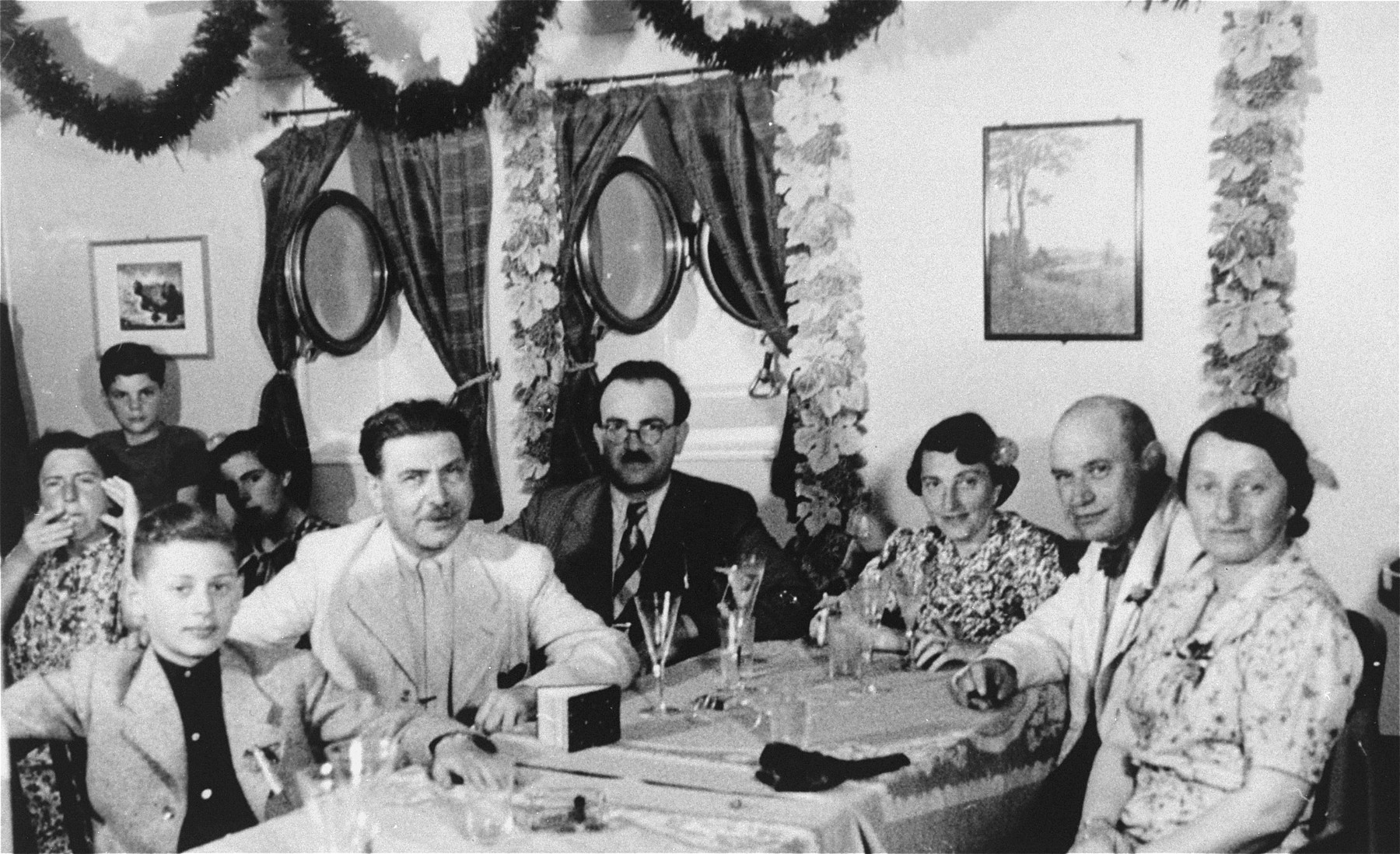 Passengers have a meal on the refugee ship MS St. Louis.    From a photo album belonging to St. Louis passenger Moritz Schoenberger.   Pictured from left to right are: Egon Salmon; Moritz Schoenberger; Paul Silzer; Erna Salmon; Julius Hermanns; and Leontine Silzer.