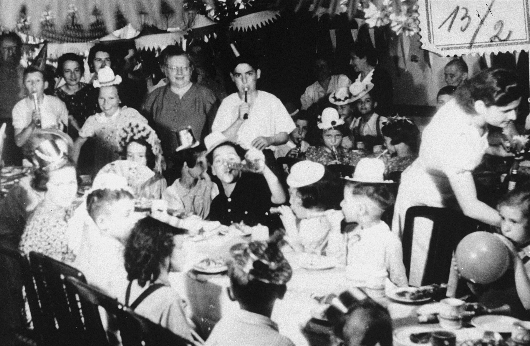Children attend a party on board the MS St. Louis celebrating the fact that Belgium, France, Great Britain and the Netherlands agreed to give visas to the passengers.    Heinz Goldstein is pictured in the center, blowing a horn.  Also pictured are Ruth Friedman, Herbert Karliner, Ruth Karliner, and Moser.