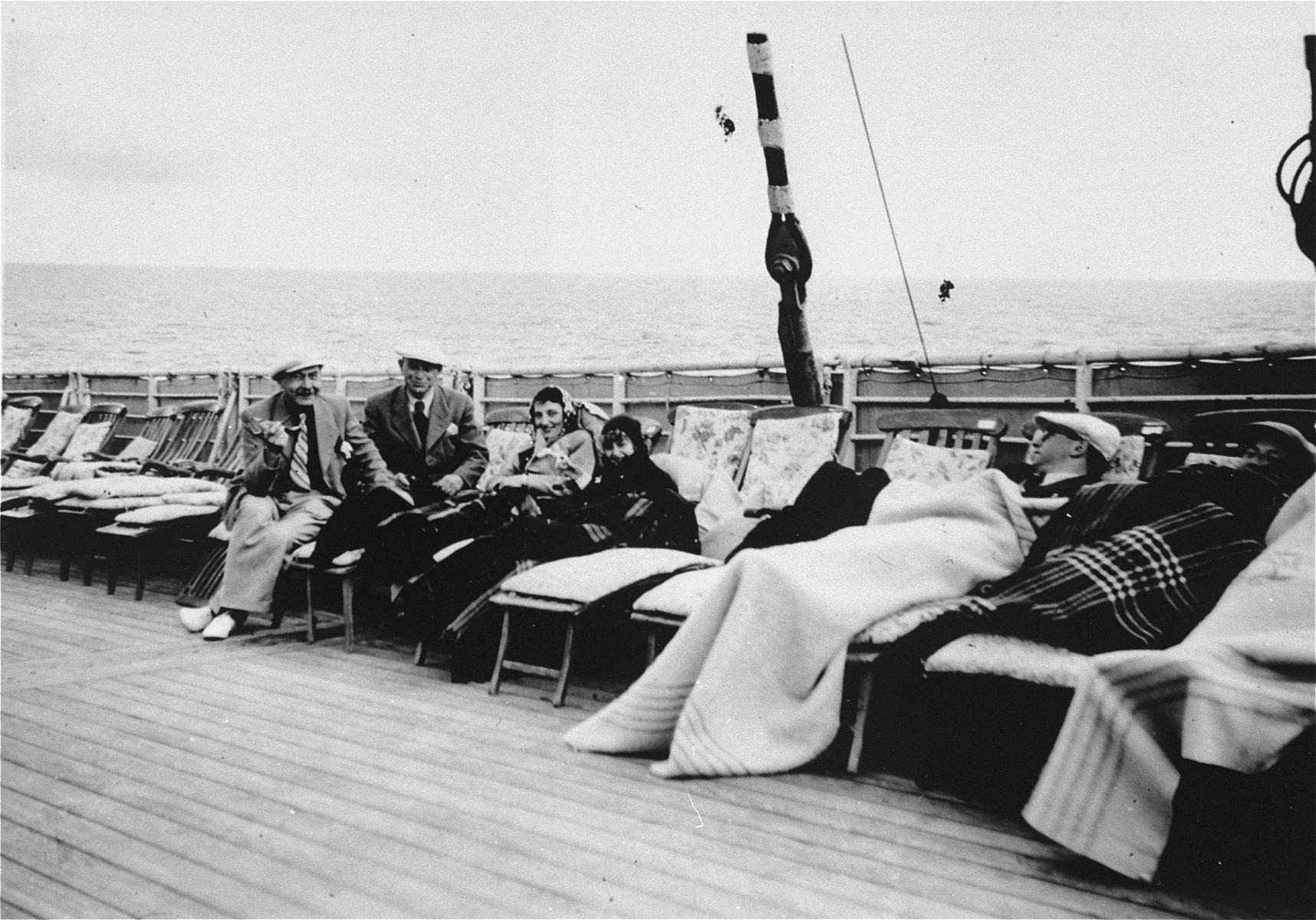 Passengers lounge on the deck of the refugee ship MS St. Louis.     From a photo album belonging to St. Louis passenger Moritz Schoenberger.