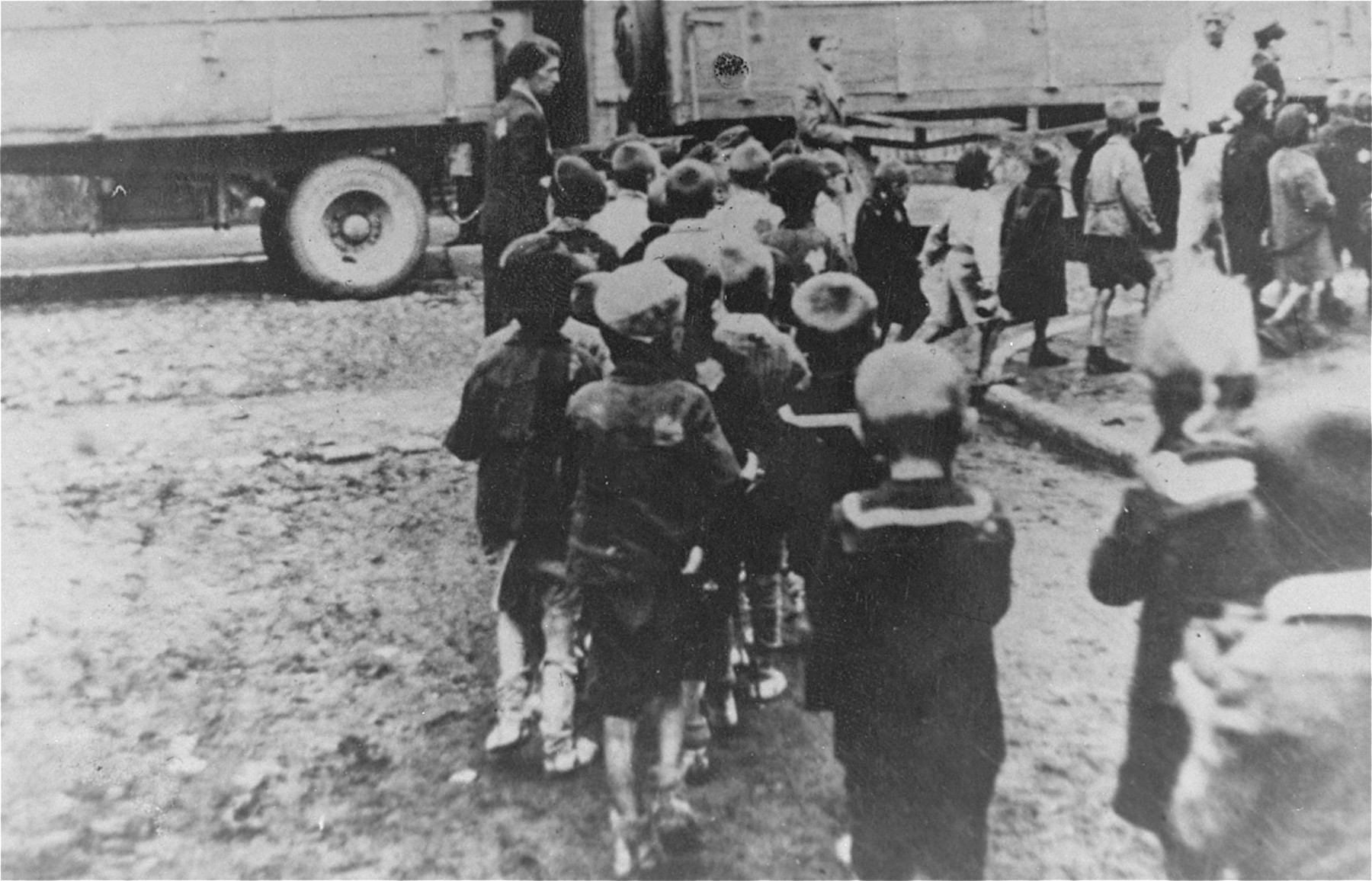 """Children from the Marysin colony who were rounded-up during the """"Gehsperre"""" action in the Lodz ghetto, walk in a line to the trucks that will transport them out of the ghetto."""