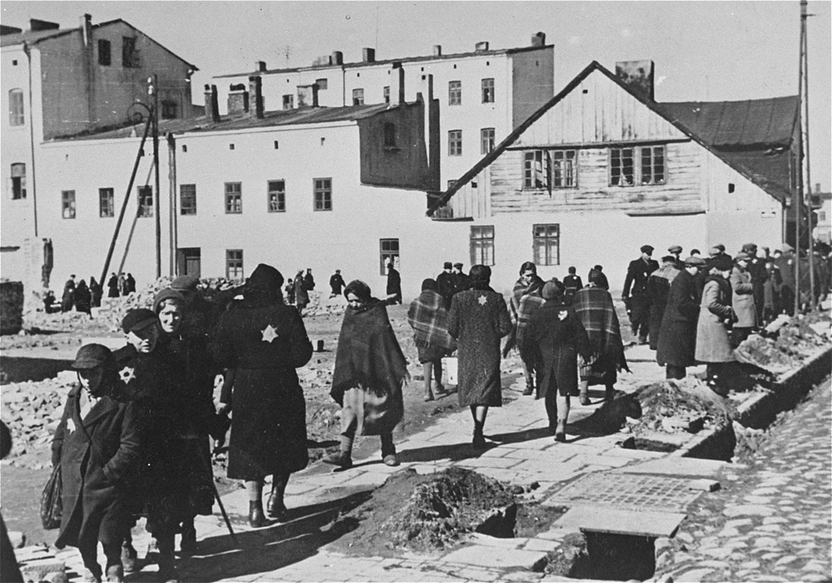 Lodz Jews walk through a courtyard filled with debris a short time before the sealing of the ghetto.  Jews in Lodz were ordered to move into the ghetto on February 8, 1940, and the ghetto was sealed on April 30, 1940. The ghetto was established in the poorest and most neglected part of town - Baluty and The Old Town (Stare Miasto).