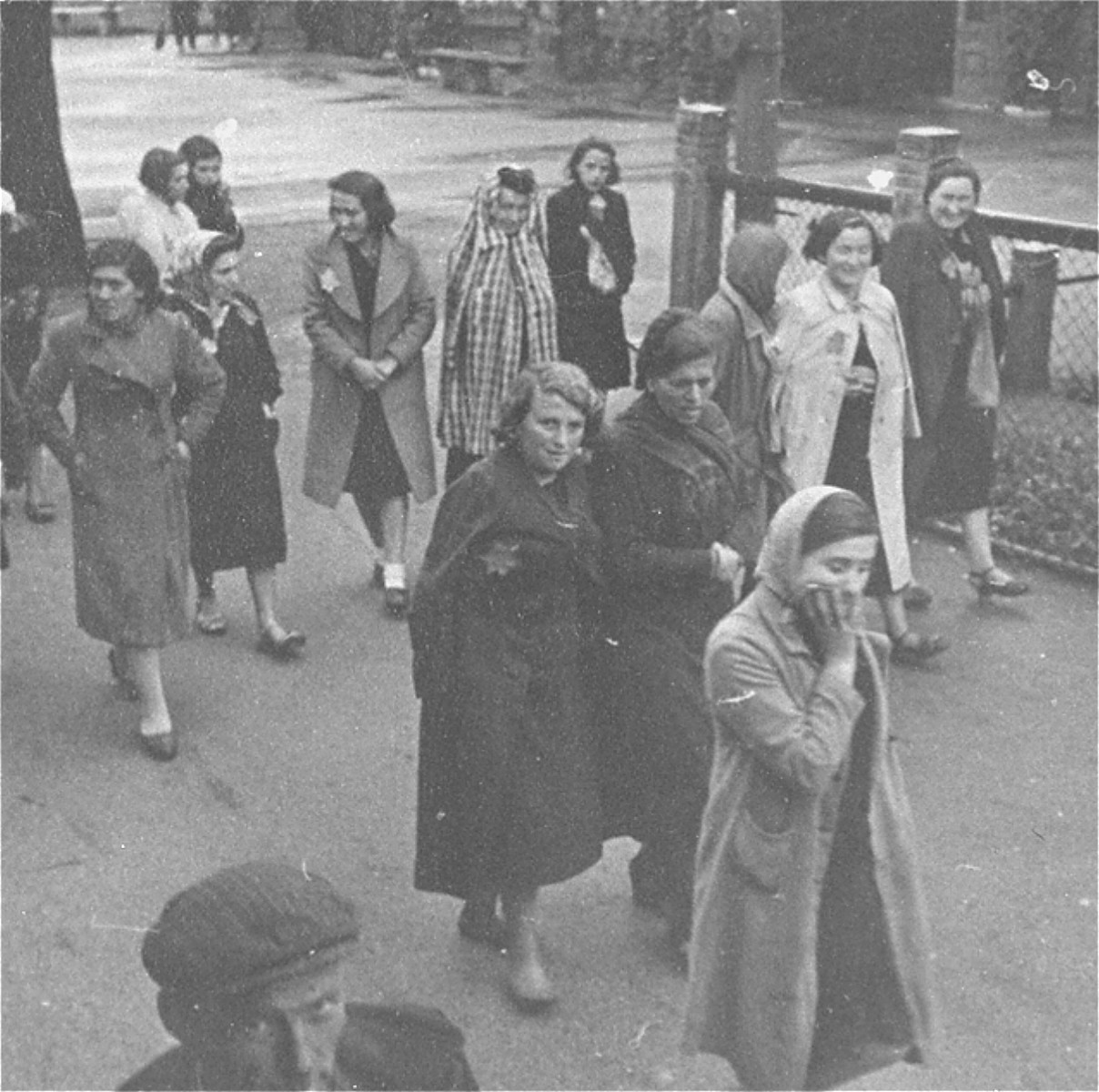 Jewish women wearing yellow stars are walking in the street, near a park.   This photo was taken before the establishment of the ghetto.
