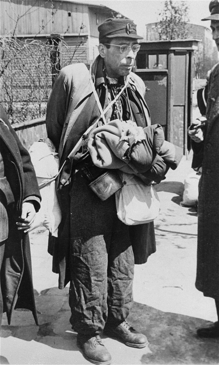 A German Jew, laden with his belongings, awaits at an assembly point for the deportation to the Chelmno death camp.    On the right  is Dr. Josef Klementynowski, an employee of the Ghetto Archives.   Approximately 20,000 German, Austrian and Czech Jews were brought to the Lodz ghetto in the fall of 1941 and deported to the death camp in Chelmno in the spring of 1942.