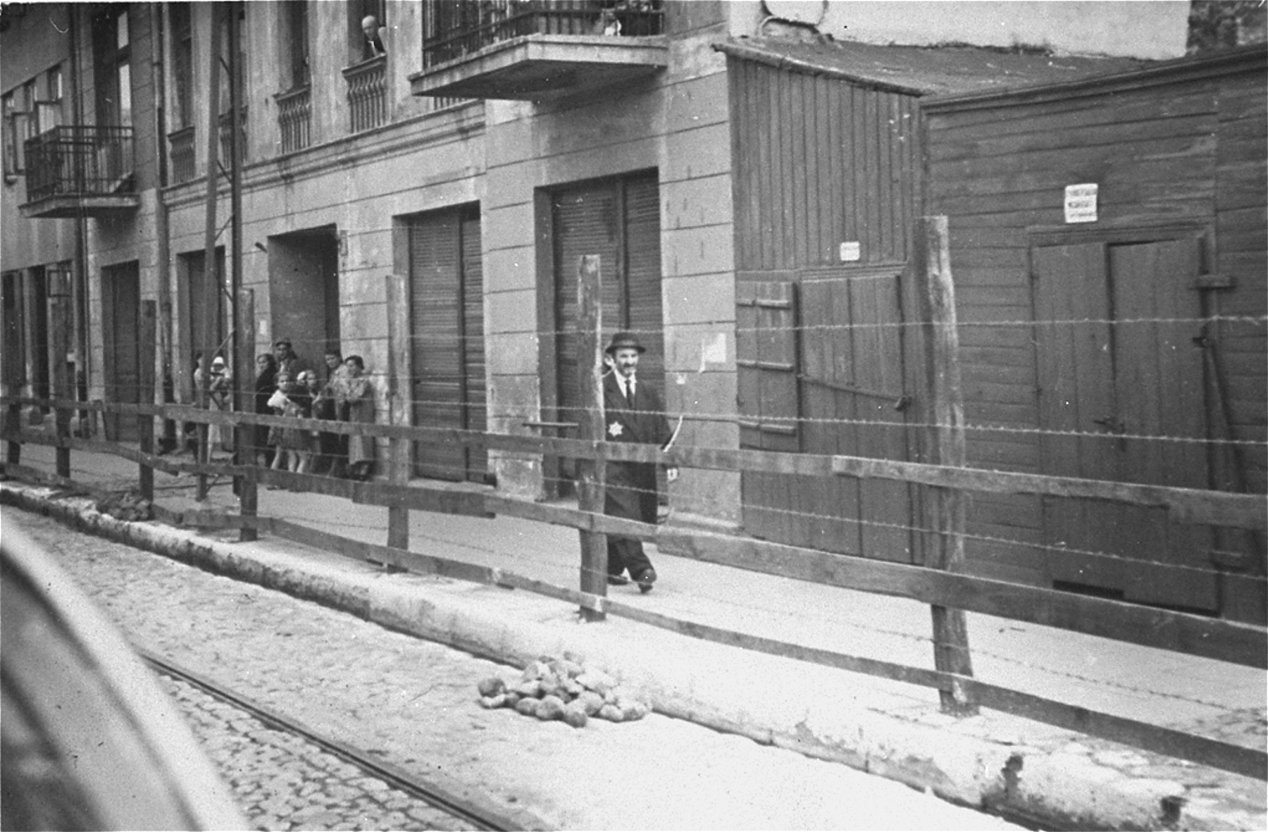 Lodz ghetto Jews behind the wooden and barbed wire fence that separated the Lodz ghetto from the rest of the city (probably taken from Zgierska Street).