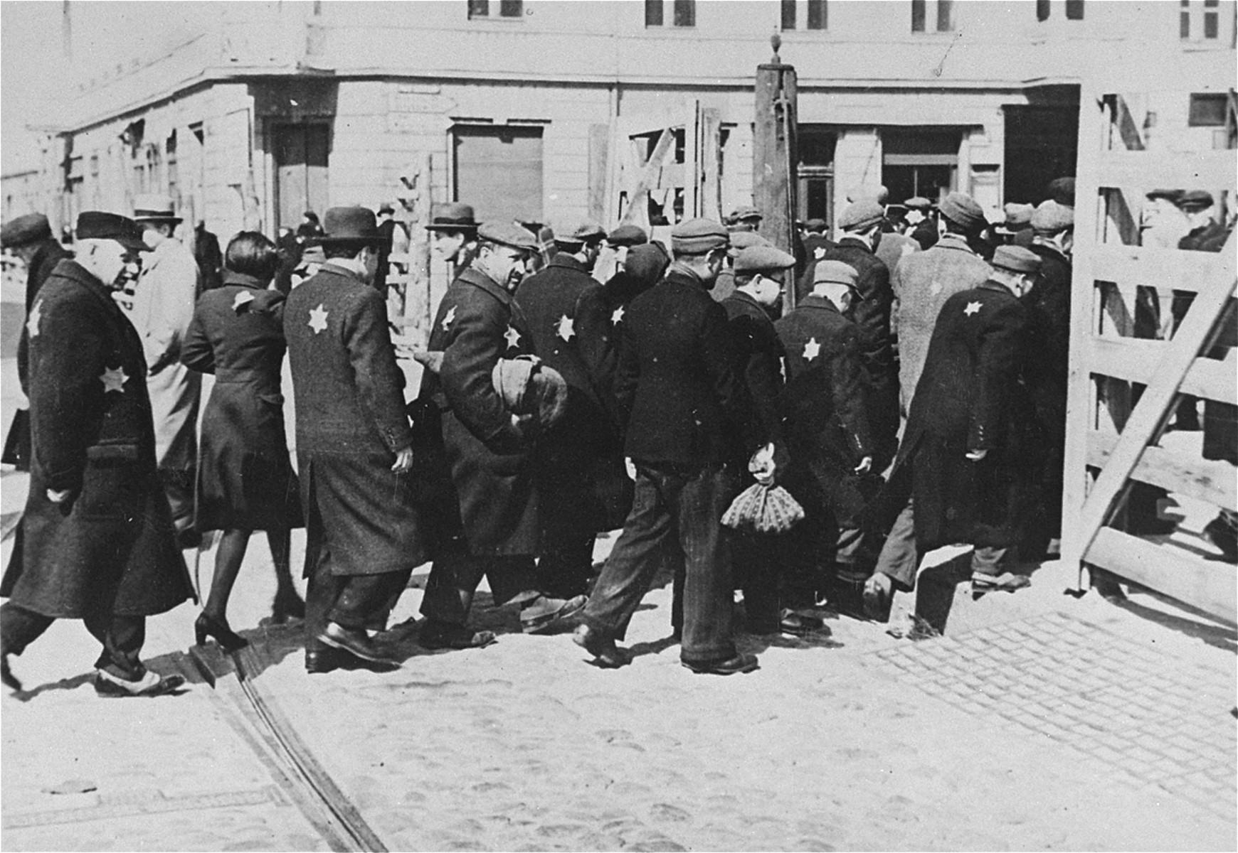 Jewish men and women entering the Lodz ghetto.