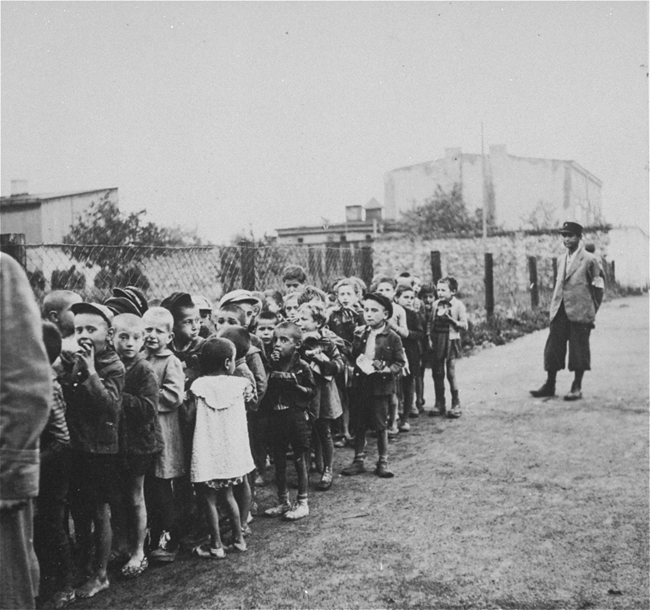 """Children from the Marysin colony who were rounded-up during the """"Gehsperre"""" action in the Lodz ghetto, march in a long column towards a deportation assembly point."""