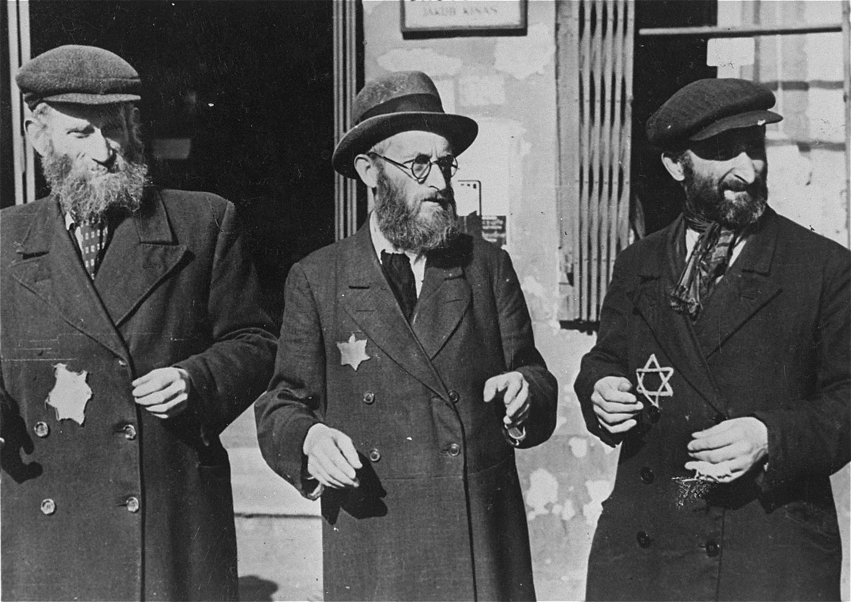 Three Jewish men stand outside a building in the Lodz ghetto.