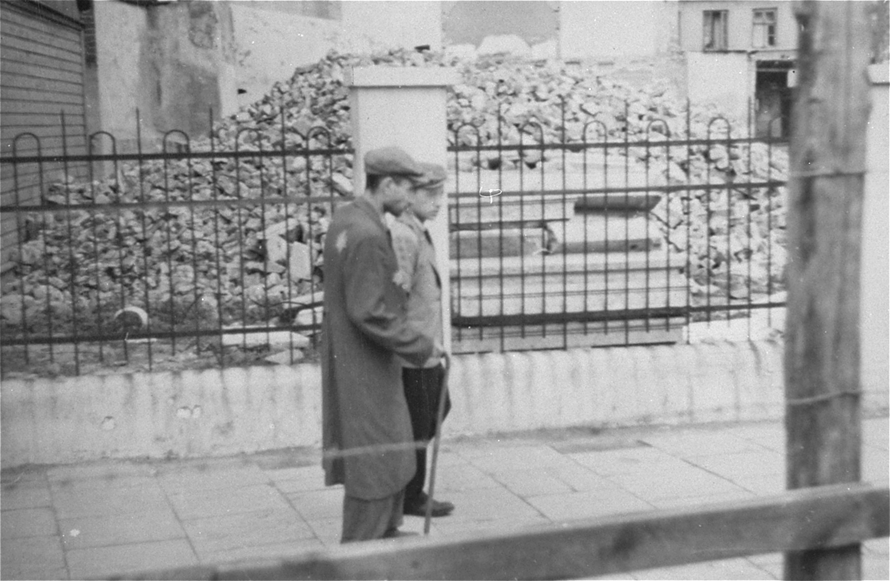 Jews in the Lodz ghetto walk down the street behind the wooden and barbed wire fence that separated the ghetto from the rest of the city (probably taken from Zgierska Street).