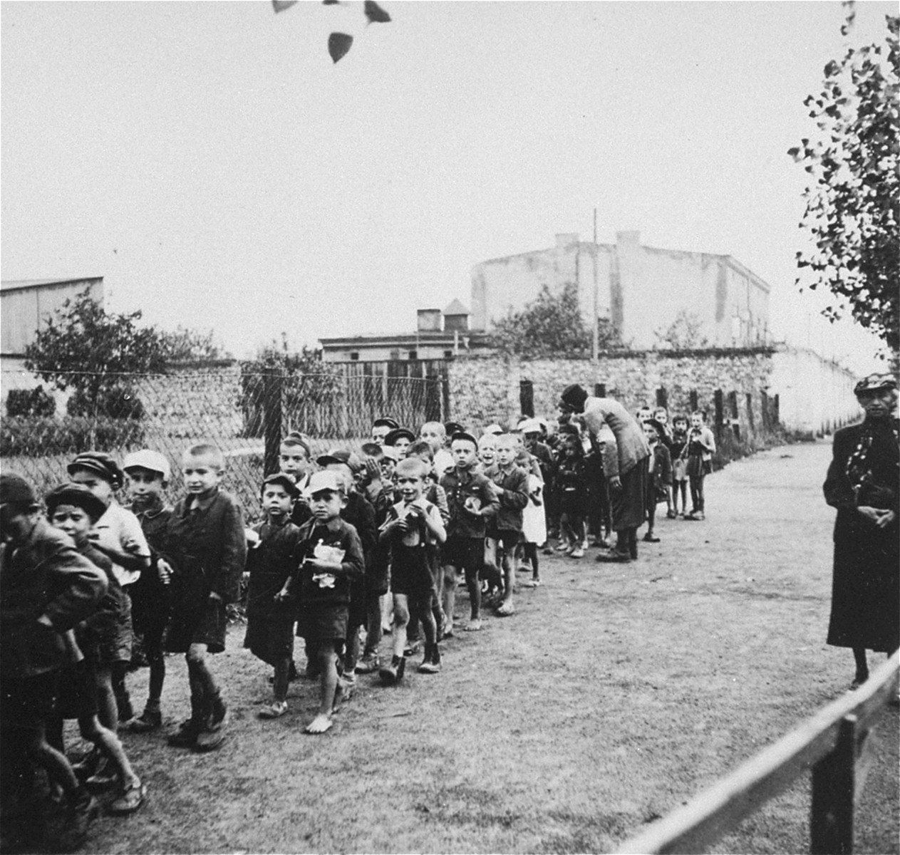 "Children from the Marysin colony who were rounded-up during the ""Gehsperre"" action in the Lodz ghetto, march in a long column towards a deportation assembly point."