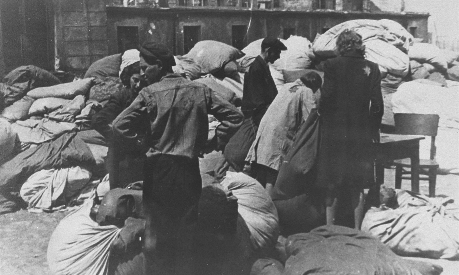 Jewish men and women prepare to sort  clothing that was confiscated from the deportees to the Chelmno death camp.
