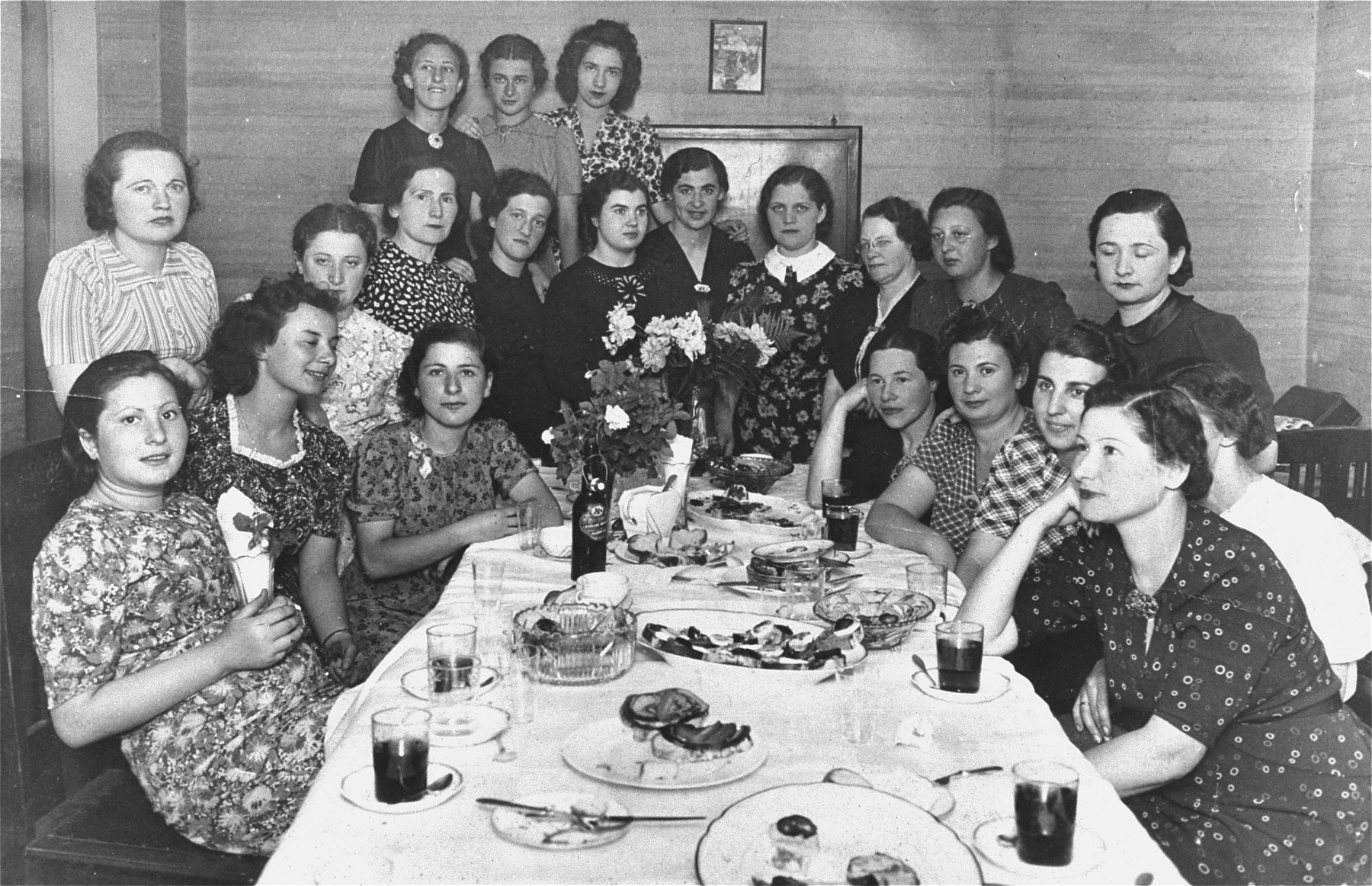 Group portrait of teachers at a social gathering.  Fruma Rachkovsky stands in the V-neck dress at the rear, in the centre.  The caption in Hebrew on the back of the photograph indicates that the photograph was sent to Fruma's brother-in-law and sister-in-law by her husband.   This photo might have marked the graduation of a sewing class.