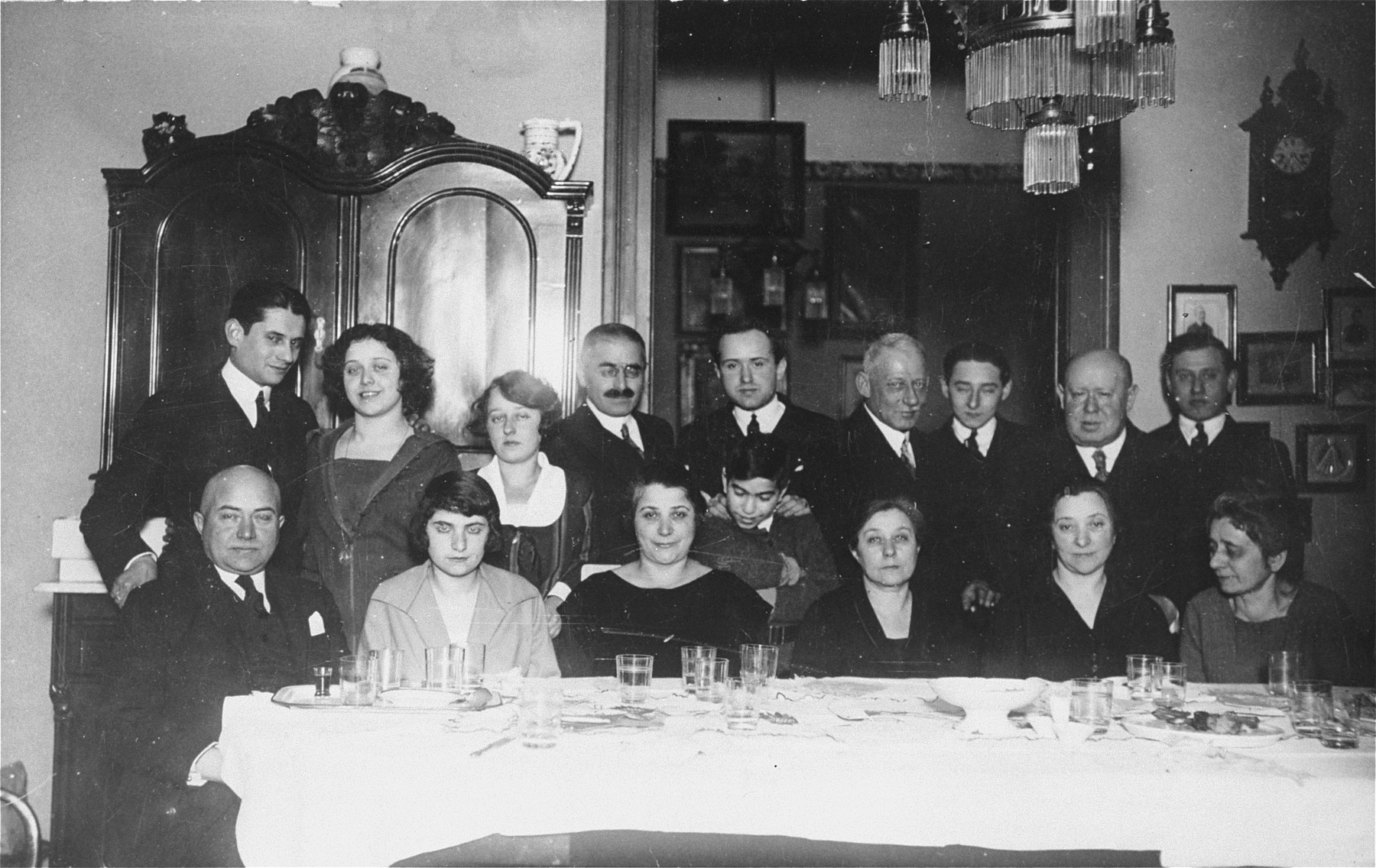 Group portrait of the extended Spitzer family in their dining room.    Pictured in the front row from left to right are: Bela Spitzer, Erzsebet Gyarto, Gizella (Spitzer) Gyarto, Malvina (Spitzer) Kornhauser, Olga (Spitzer) Kulka and Szeren Spitzer.  In the second row from left to right are: Lajos Ritcher, Rozsa (Kulka) Ritcher, Margit Kornhauser, Marcell Gyarto, Jeno Kulka, Samu Kornhauser, Laszlo Kornhauser, Fulop Kulka and Karoly Kornhauser.  The young boy in the middle is Tibor Gyarto.