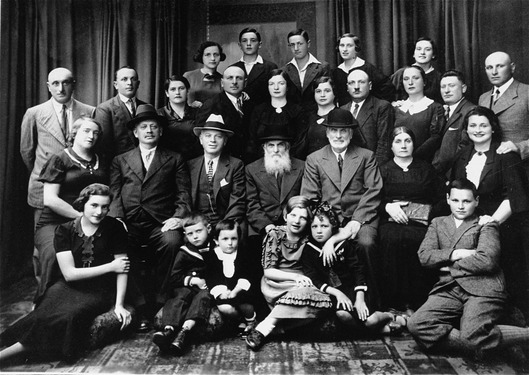Group portrait of members of the Solski family taken during a family gathering in honor of two visiting great uncles, one from South Africa and one from America.  Rella Solski is the child pictured in the front row in the sailor suit.  Rella Solski (donor) and her cousin, Mina Braudh were the only survivors.   Bottom row, left to right Moshe Solski Label Solski Rella Solski, daughter of Chatzkel Eta Rella, cousin of donor Rella, donor Kera Solski, cousin of donor  Second row from bottom, left to right Dina Solski, aunt of donor, Peretz's wife Wolf Solski, uncle from South Africa Joe Saul, uncle from United States Zusal Solski Abe-y Solski, donor's grandfather Donor's step-grandmother Mania Solski, wife of Solomon  Third row from bottom, left to right Peretz Solski, donor's uncle on father's side, husband of Dina Chatzkel Solski, donor's uncle on father's side Chaja Solski, donor's aunt, pregnant in picture Joe Solski, husband of Gita, father of Label and Eta Rella Gita Solski, wife of Joe Solski, mother of Label and Eta Rella Dina Solski, donor's mother Zusel Solski, donor's father Rivka Braudh, donor's aunt on father's side Alter Braudh, Rivka's husband Solomon Solski, Mania's husband  Fourth row from bottom, left to right Mina, daughter of Dina and Peretz Charles, brother of donor Label, son of Dina and Peretz Brira Braudh, son of Rivka and Alter Mina Braudh, daughter of Rivka and Alter