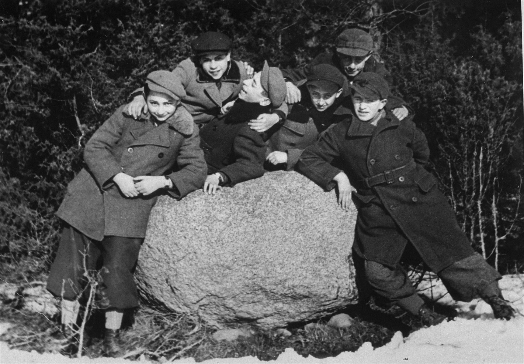 A group of school-age boys poses next to a boulder in the town of Eisiskes.  The Jews of this shtetl  were murdered by the Einsatzgruppen on September 21, 1941.