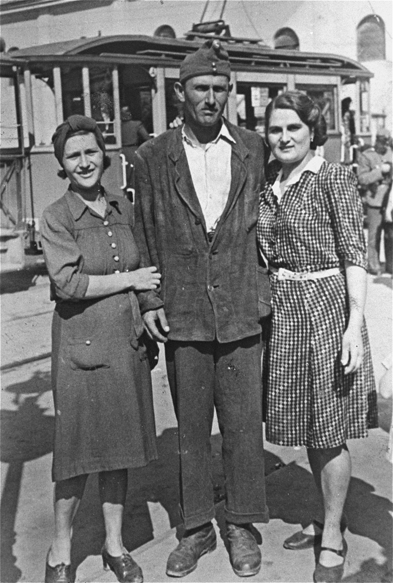 A Jewish member of the Hungarian labor service poses on a street in Oradea with his two sisters.  Pictured from left to right are Chaye (Wolf) Sure, Mendel Wolf and Irene (Wolf) Bryks. The family was originally from Toshnad, Romania.