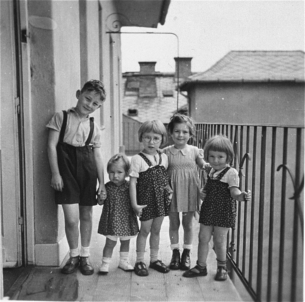 A group of children poses on the balcony of an apartment in Budapest.  Pictured are Gyorgy Pick (left), with his cousin, Clara Kornhauser (second from the left), and three non-Jewish neighbors.