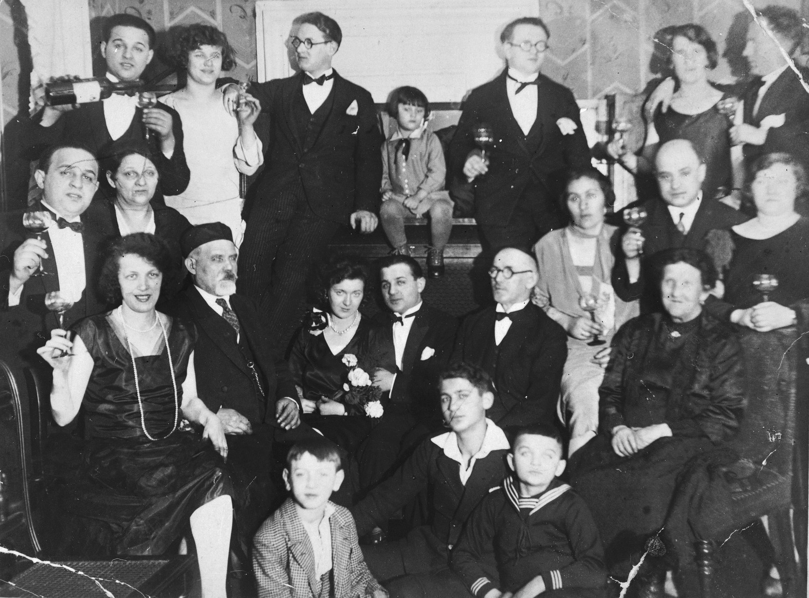 Group portrait of friends and relatives offering a toast at a Ginsburg family celebration.