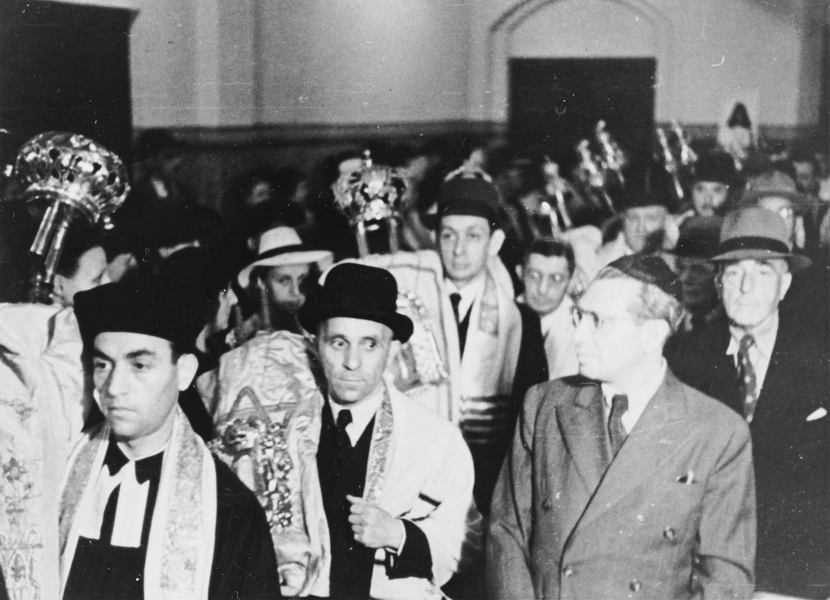 A procession of men carrying Torah scrolls into the  opening services of the Pestalozzistrasse synagogue in Berlin - Charlottenburg, held on Erew Rosh Hashana.     Among those pictured are the donor's father Hans Fabian (center), Kantor Estrongo Nachama (far left) and  Fritz Sachs (far right).  Kantor Nachama was a survivor of Auschwitz.  Fritz Sachs was a member of the synagogue board (Gabbai).
