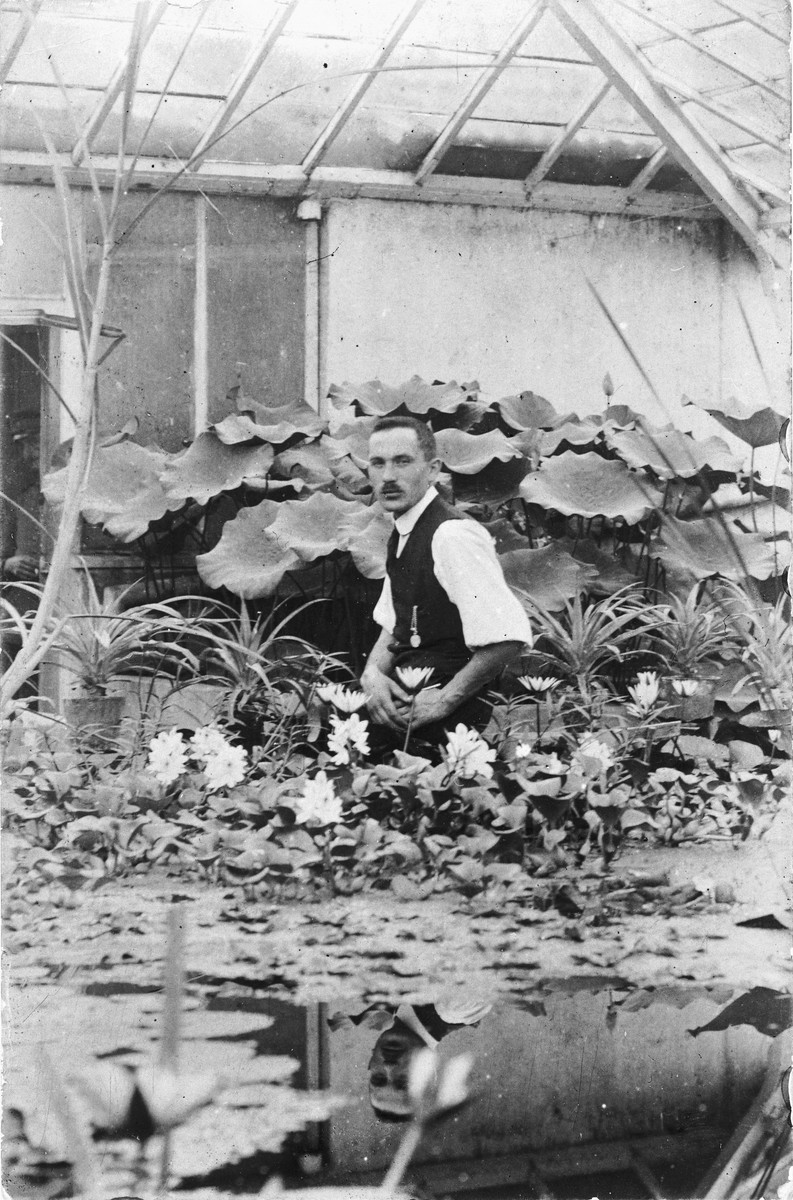 Josef Ginsburg poses among the water lilies in his greenhouse.