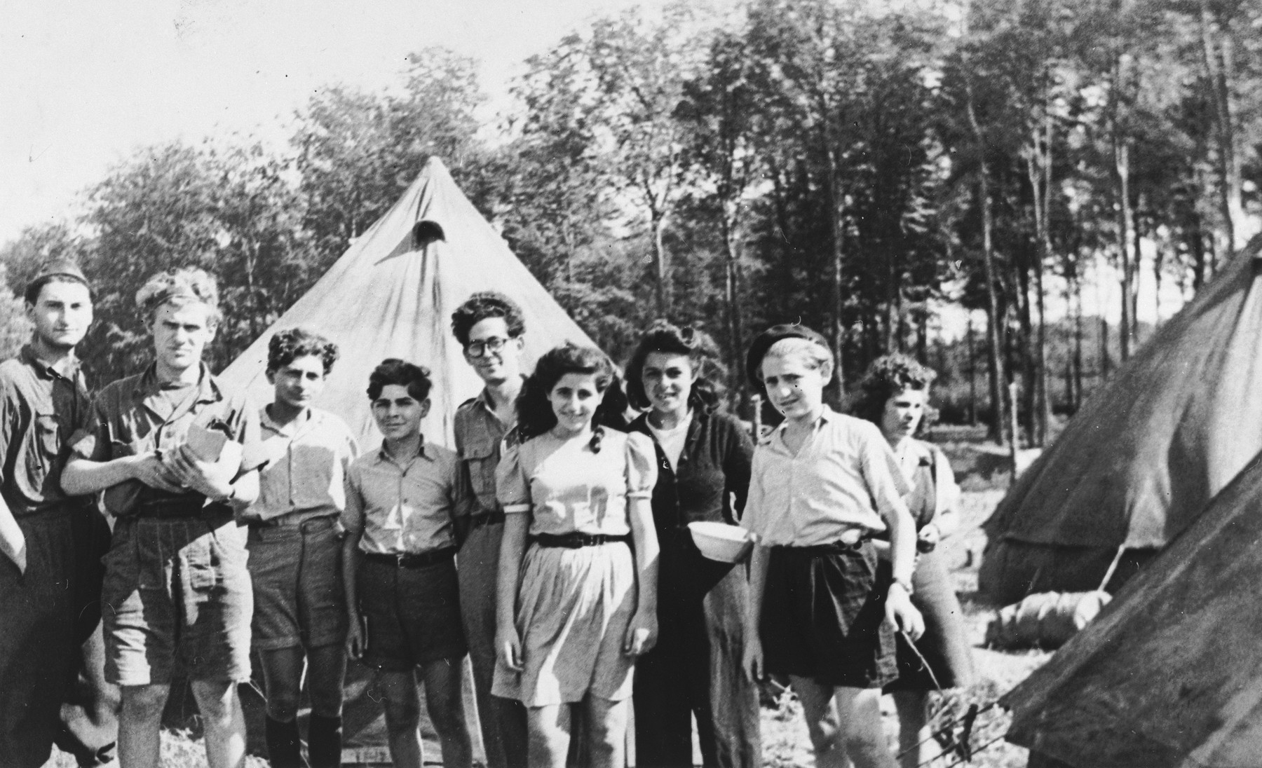 Group portrait of Jewish DP youth standing among a cluster of tents at the Poppendorf displaced persons camp.  Those pictured include Benno Ginsburg (second from the left) and Jacques Rabinovich (center, wearing glasses).