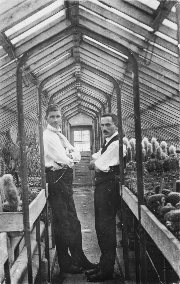 Josef Ginsburg and an assistant pose between rows of cactus plants in his greenhouse.