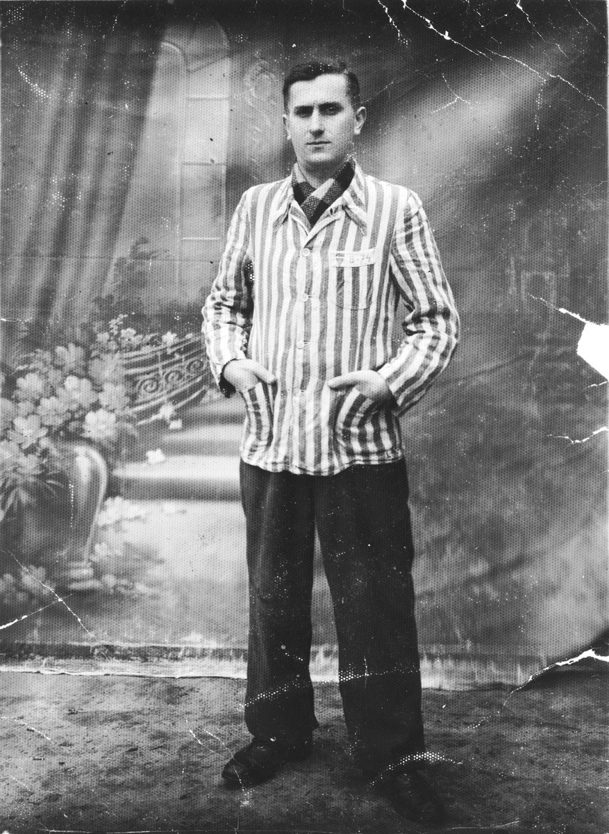 Studio portrait of David Bajer wearing the jacket of his concentration camp uniform, taken shortly after his liberation.