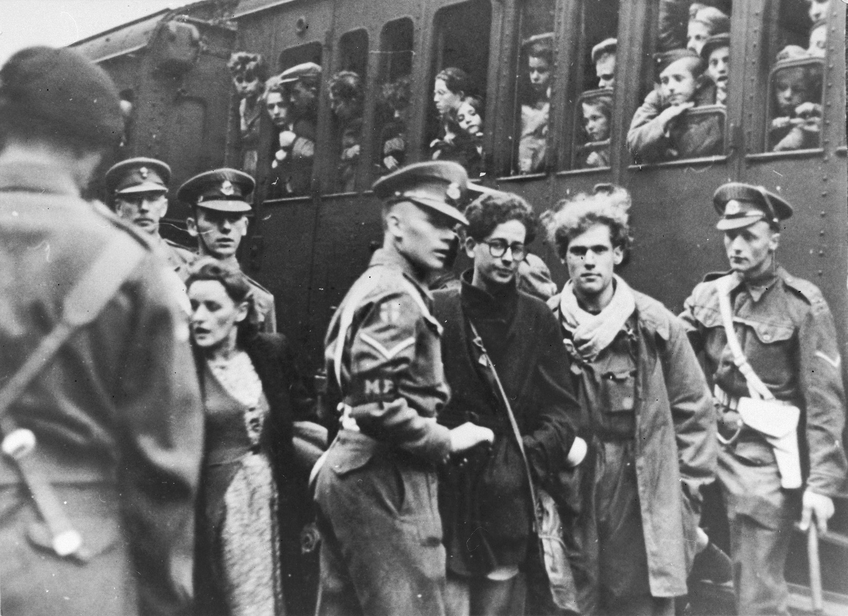 British police escort two former passengers of the Exodus 1947 who were brought back to Europe, at the train station in Hamburg.  Pictured are Benno Ginsburg (right) and Jacques Rabinovich (left, wearing glasses).