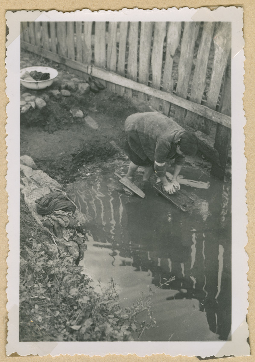 A Jewish woman wearing an armband washes clothes outside in an unidentified ghetto in Poland.